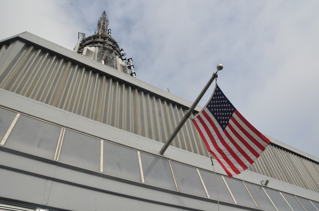 The tower of the Empire State Building, with an American flag